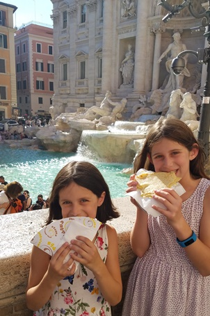 girls eating at Trevi Fountain